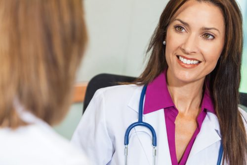 Happy, smiling, woman doctor in white lab coat with stethoscope in hospital office meeting with female colleague