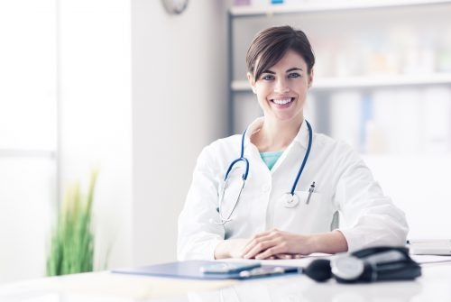 Female doctor working at office desk, she is smiling at camera, healthcare professionals